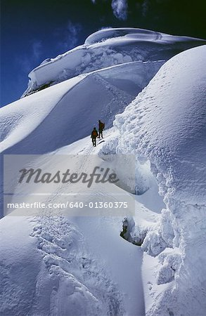 Angle View Of Two Hikers Climbing On Snowy Mountain Peak Stock Photo