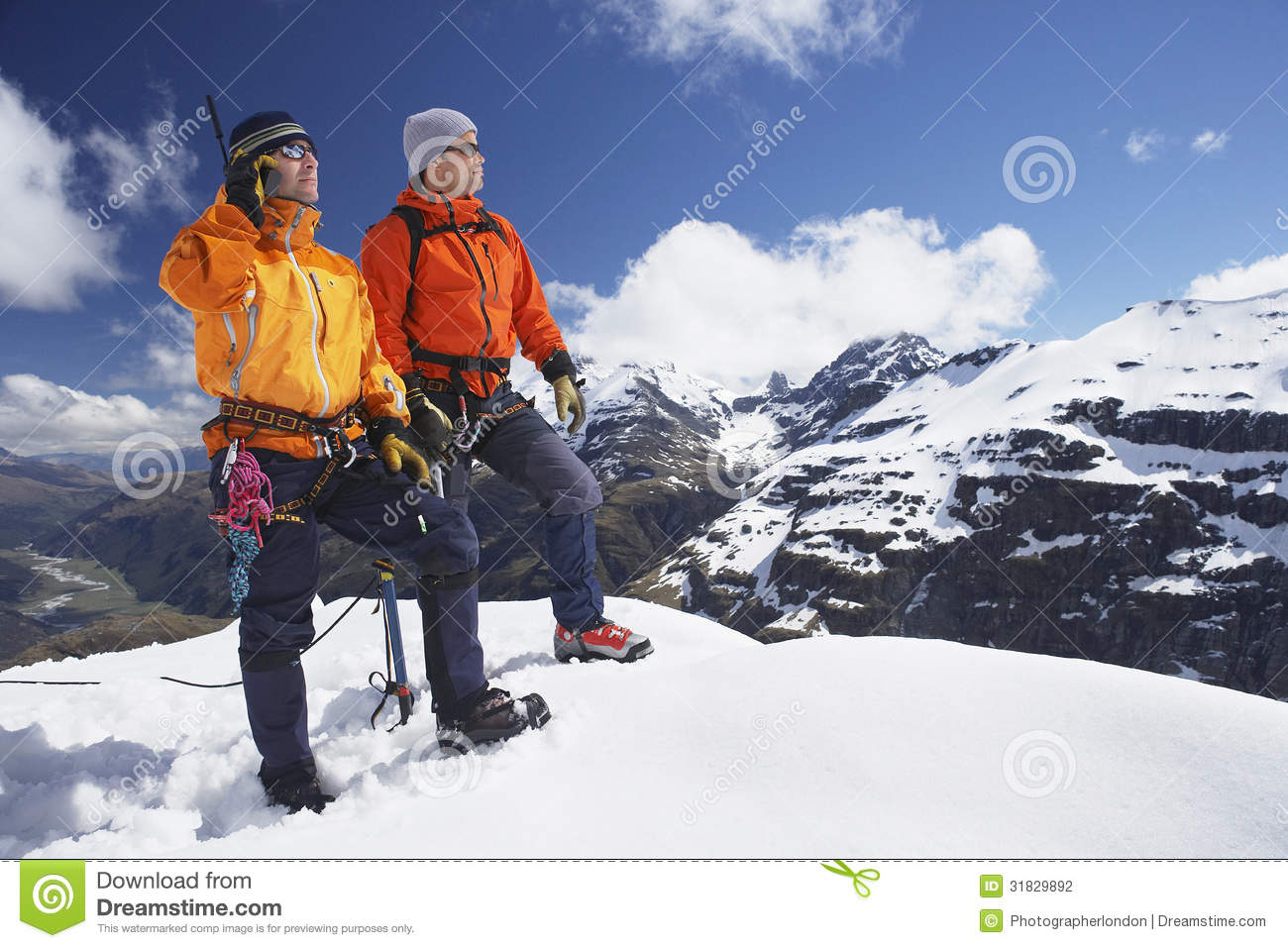 Two Male Mountain Climbers On Snowy Peak Against Sky With One Using