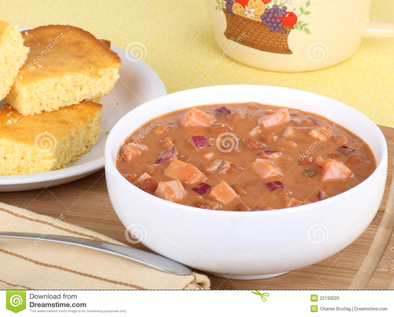 Bowl Of Ham And Bean Soup With A Plate Of Corn Bread In Background
