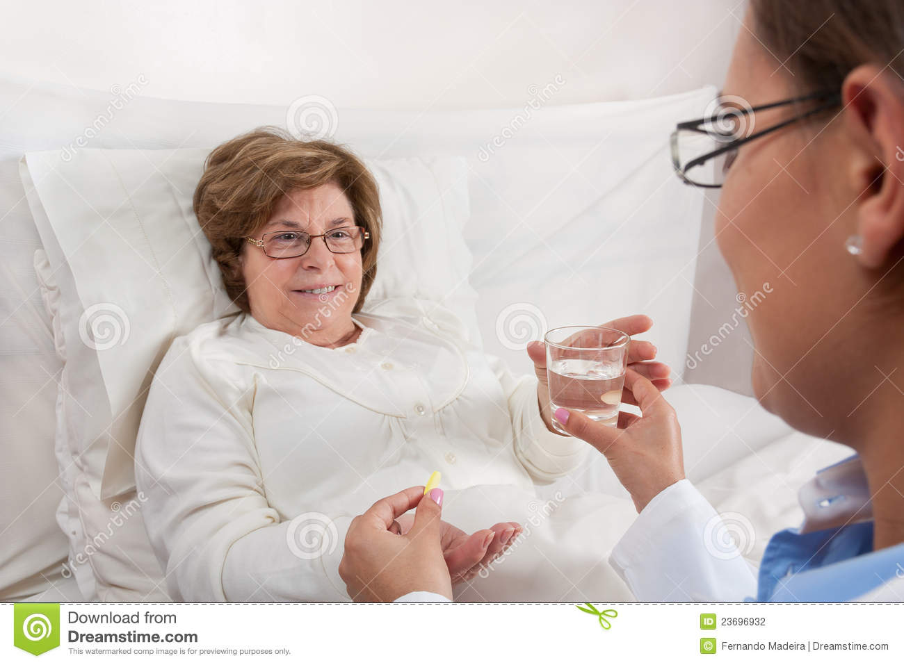 Doctor Sitting In Bed Gives Medication And A Glass Of Water To