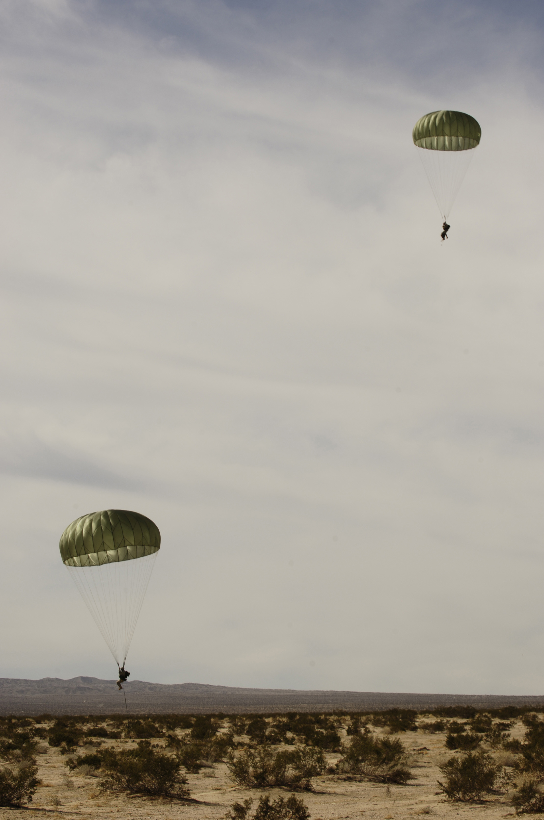 Image  Two Army Soldiers Falling With Green Parachutes Into The Desert