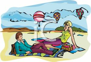 Two People Relaxing On The Beach Near Hot Air Balloons   Royalty Free