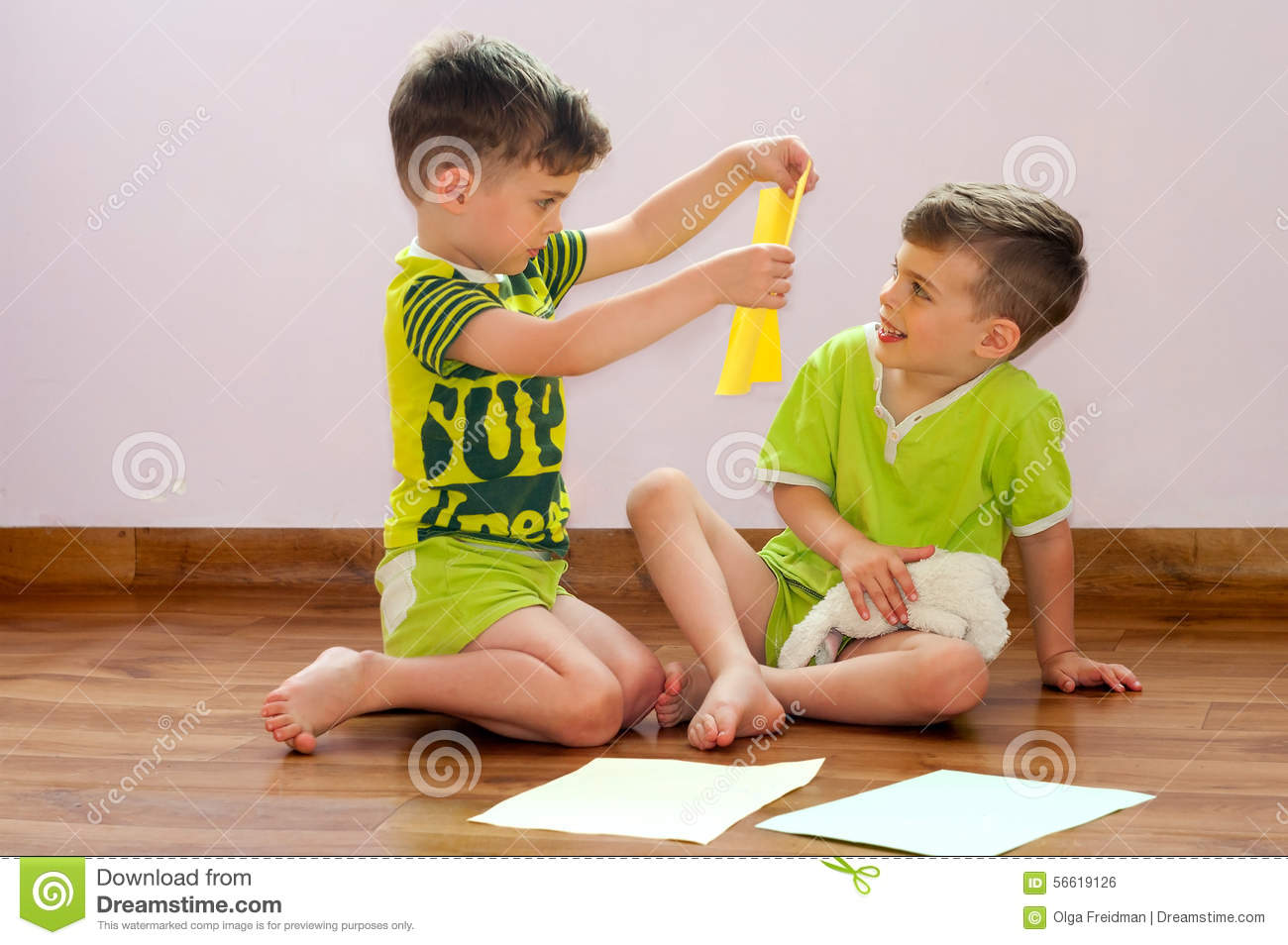 Three Year Old Identical Twin Boys Play With Paper Sitting On The