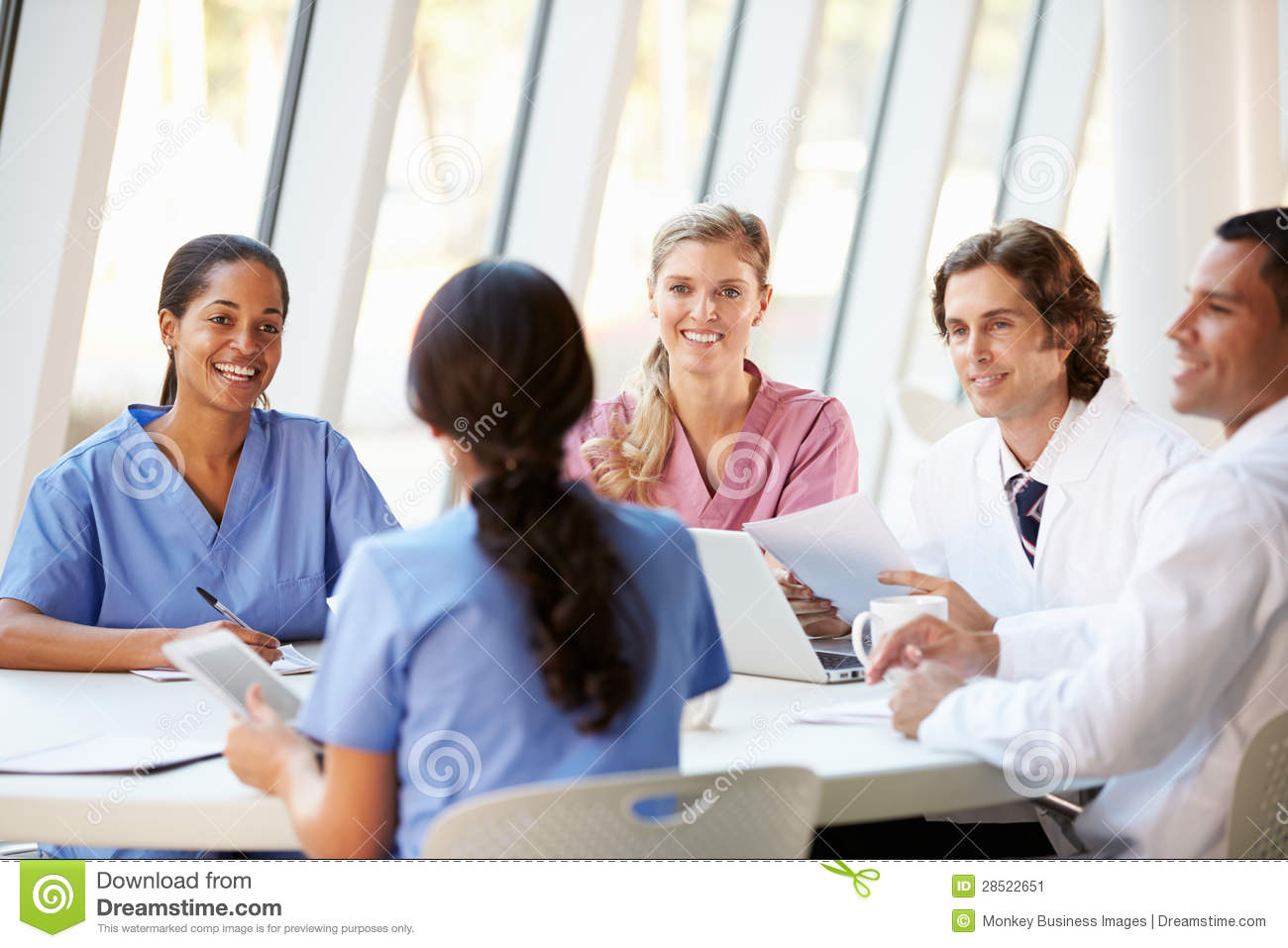 Medical Team Meeting Around Table In Modern Hospital Stock Image