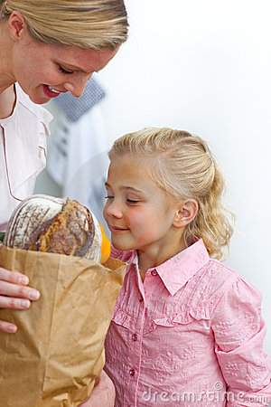 Little Girl Unpacking Grocery Bag With Her Mother Royalty Free Stock
