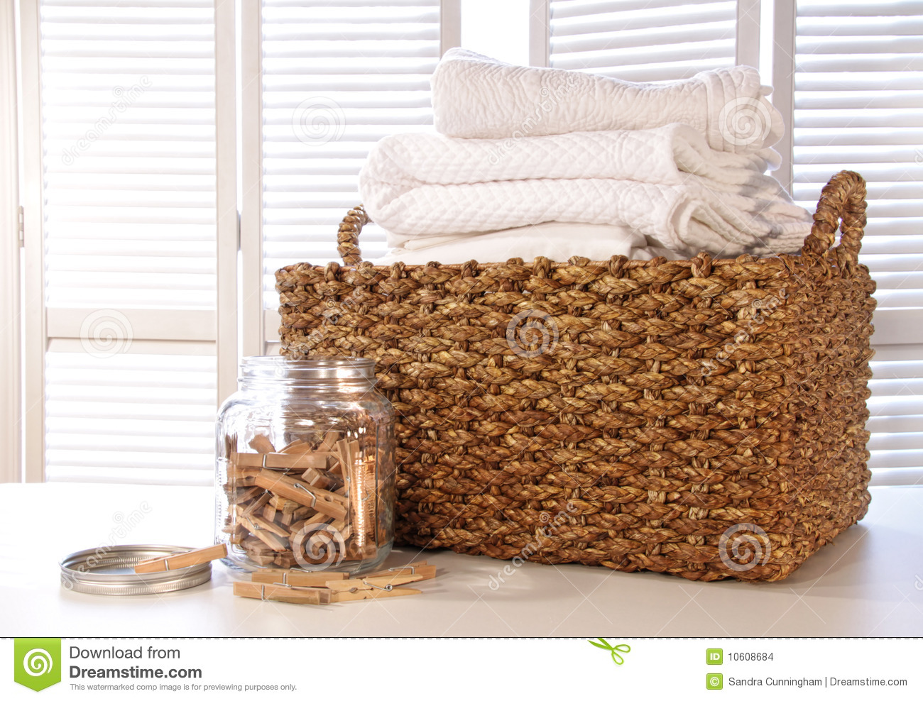 Laundry Basket With Linens On Table With Clothespins In Jar