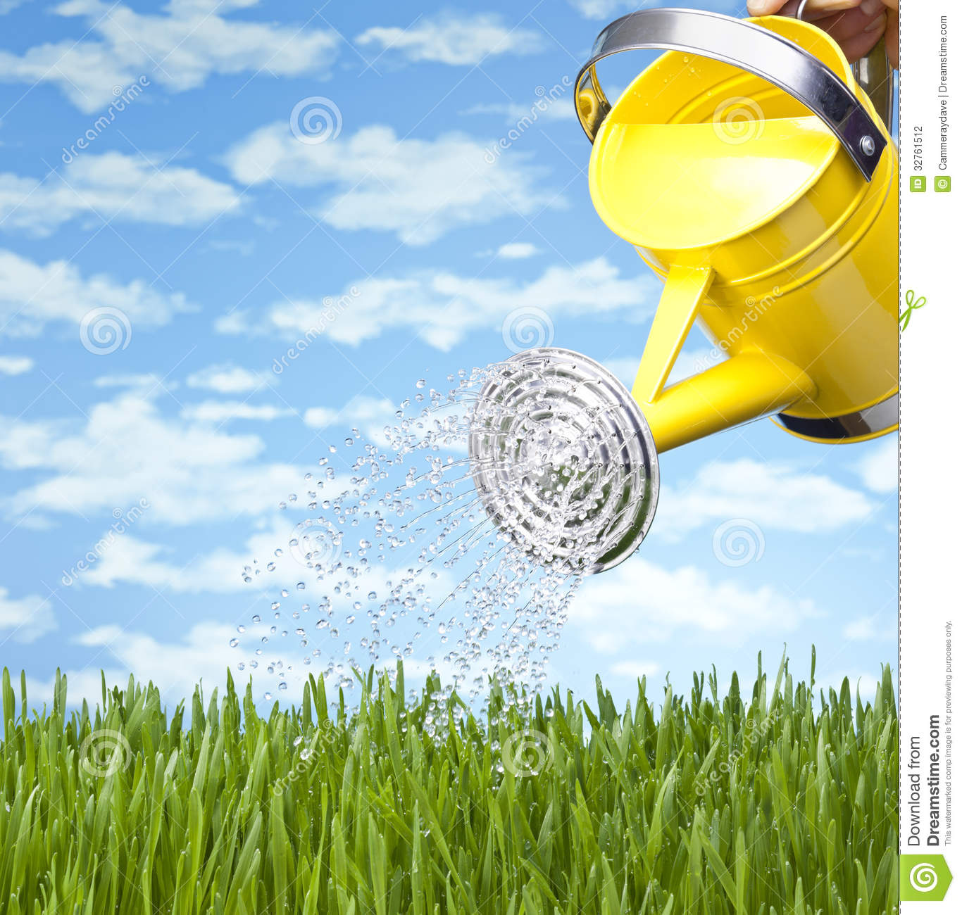 Yellow Watering Can Sprinkling Water On A Grass Lawn With A Blue Sky