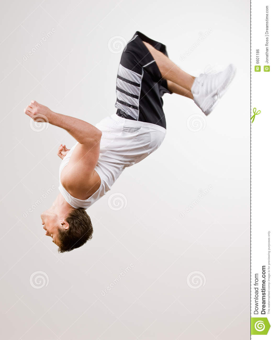 Skilled Athlete Doing Somersault In Mid Air Royalty Free Stock Image