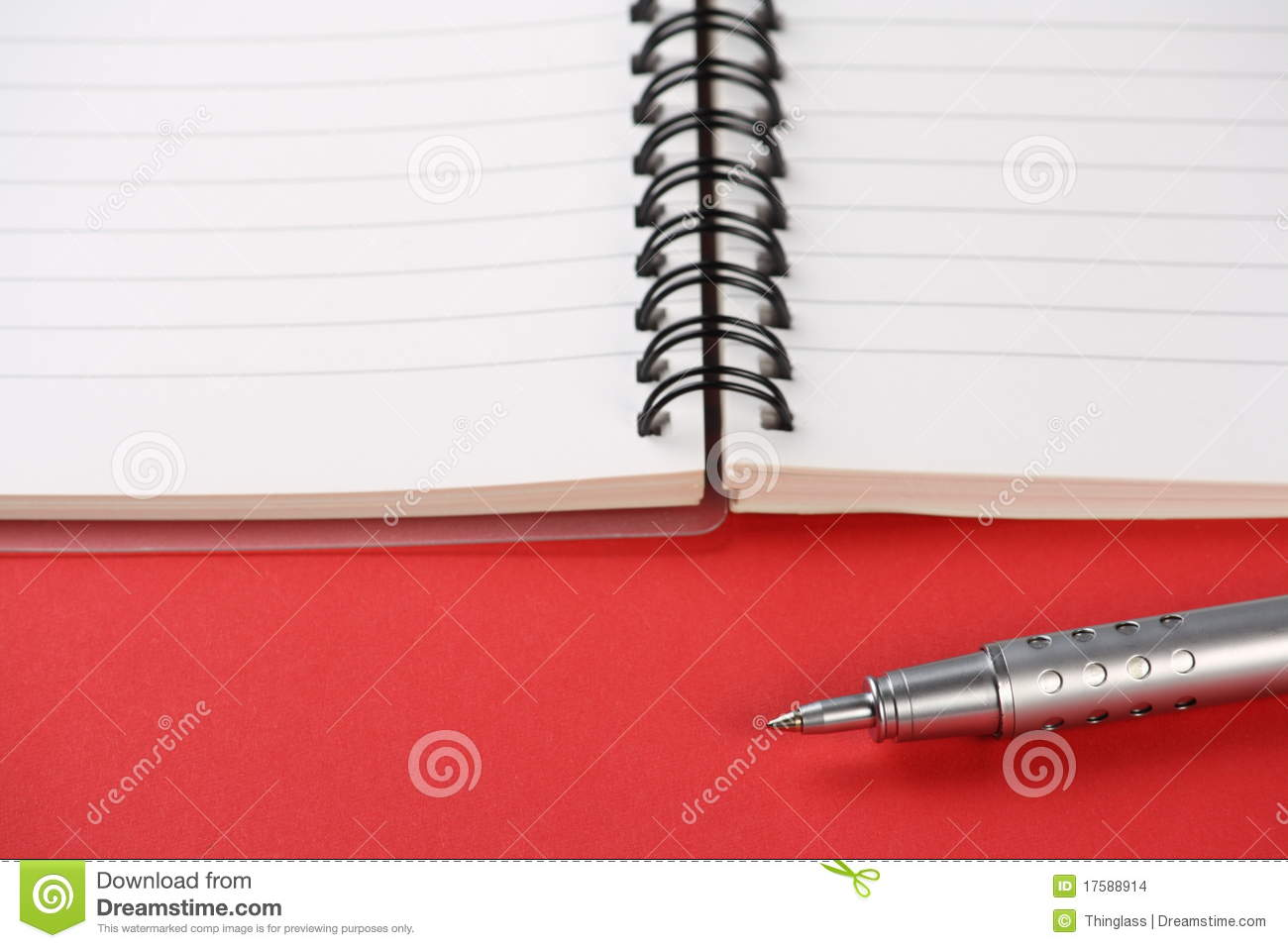 Spiral Bound Notebook And Modern Pen On A Red Paper Background