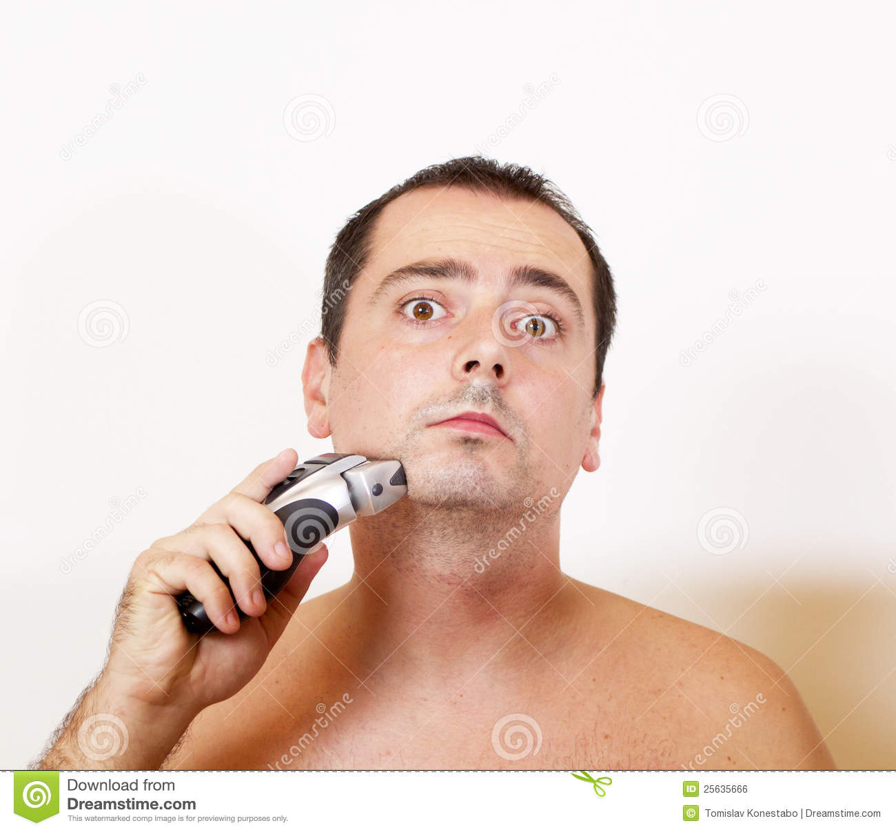 Man Shaving His Beard With An Electric Razor Royalty Free Stock Image