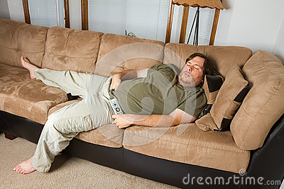 Fat Man Sleeping On The Couch With His Hand Down His Pants