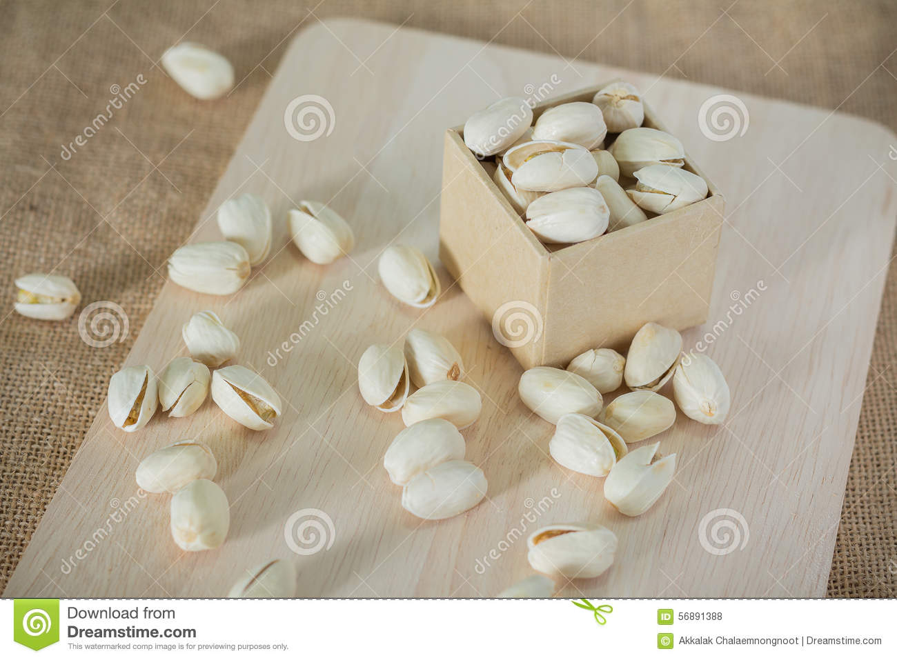 Salty Pistachios Nuts On Rustic Wooden Block