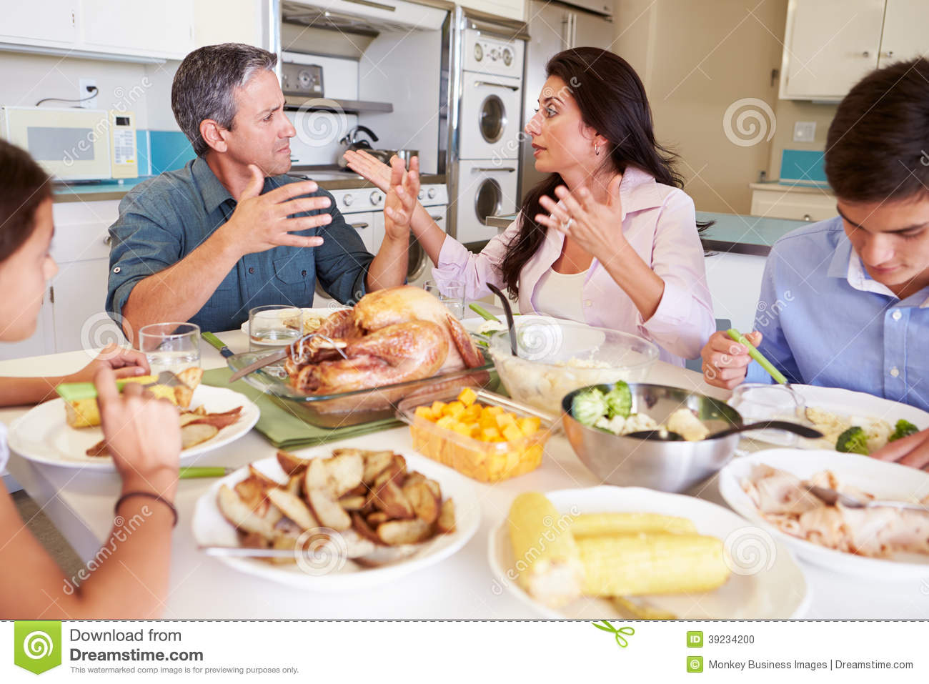 Family Having Argument Sitting Around Table Eating Meal Stock Photo