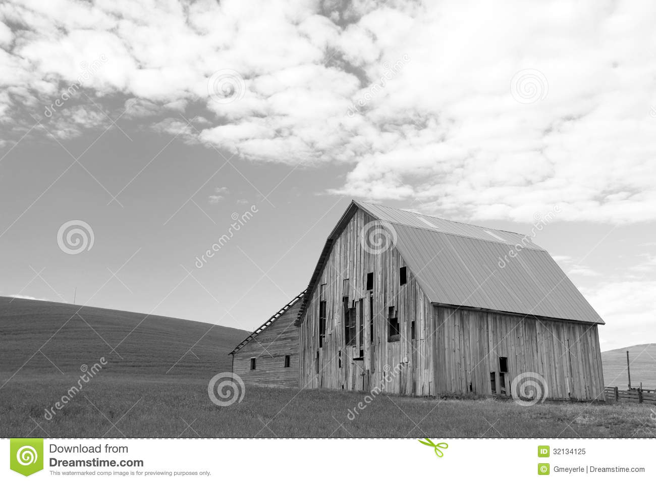 Barn In Hilly Field With Sky Filled With Puffy Clouds In Background