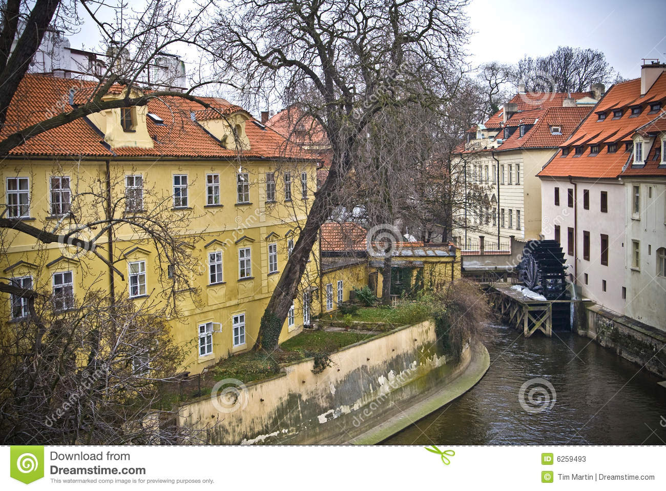 Waterwheel Mill By Homes In A Canal In Downtown Prague