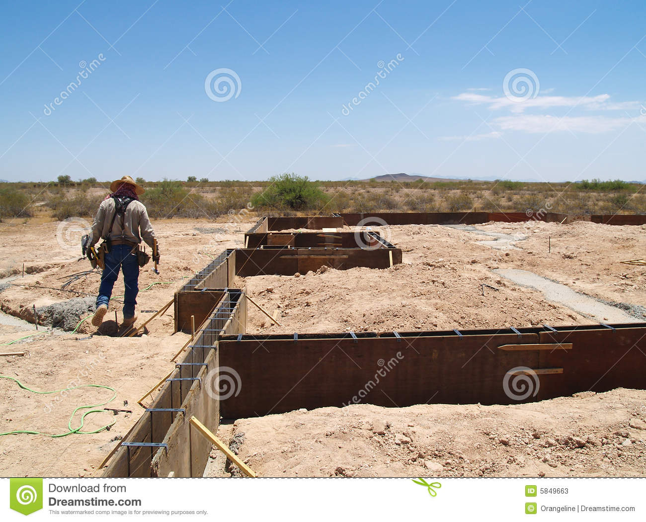 Worker Is Working On An Excavation Site  He Is Walking Over A Trench