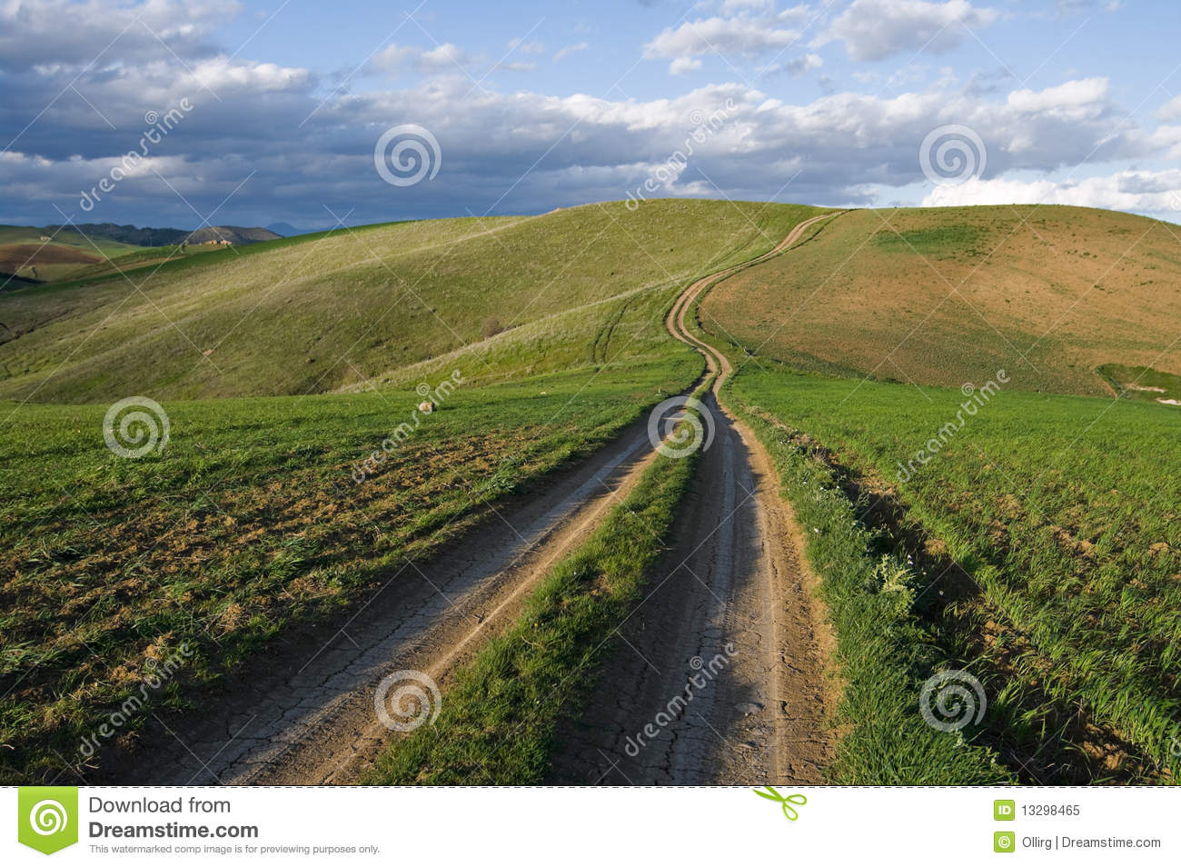 Dirt Road Long And Twisted Leading On Top Of The Green Hills At The