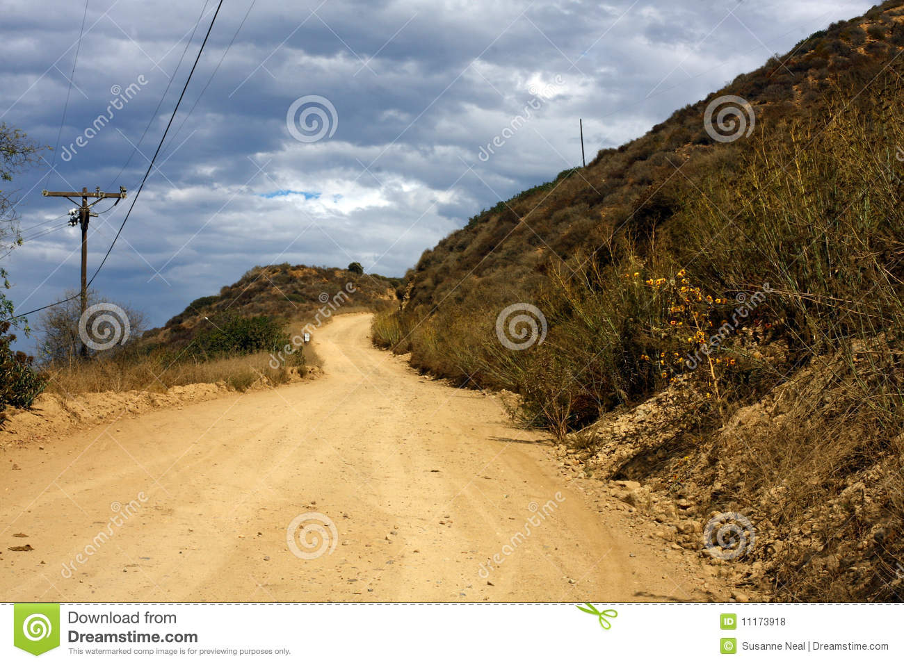 Dirt Road On Hill And Dark Blue Clouds Royalty Free Stock Photos