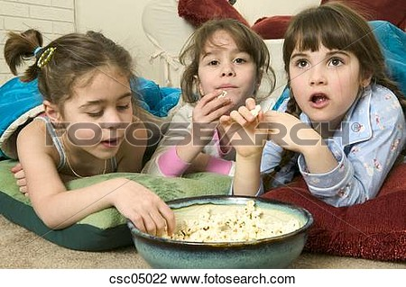 Stock Photo   Young Girls Eating Popcorn At A Sleepover  Fotosearch