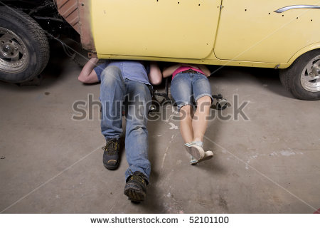 Man And Woman Working Under A Car Together With Their Legs Sticking