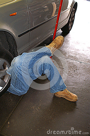 Man With His Legs Crossed As He Works Under A Car