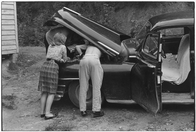 Two Men Working Under Car Hood  Young Woman Leaning On Fender Watching