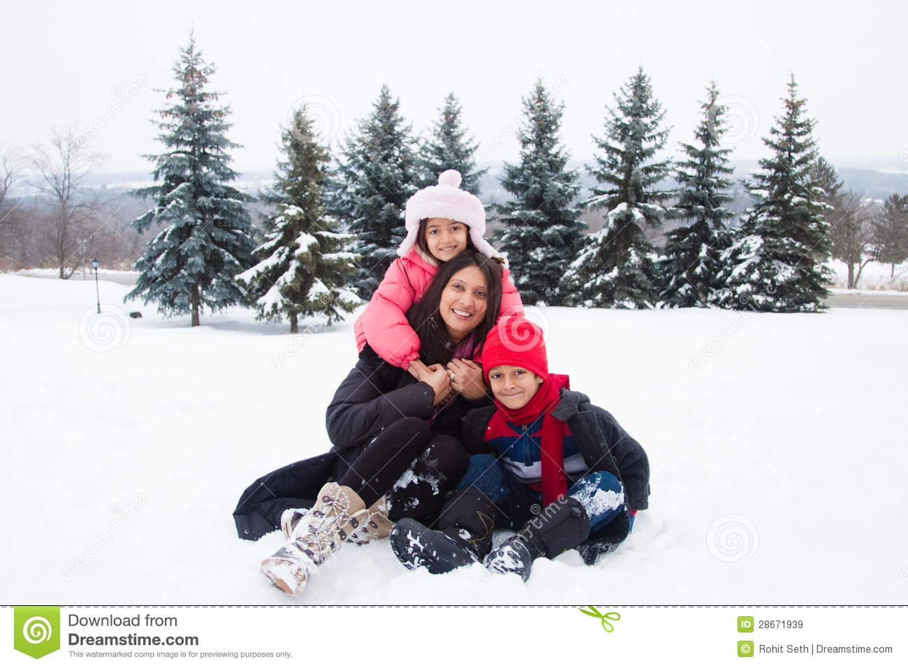 East Indian Family Playing In The Snow Royalty Free Stock Images