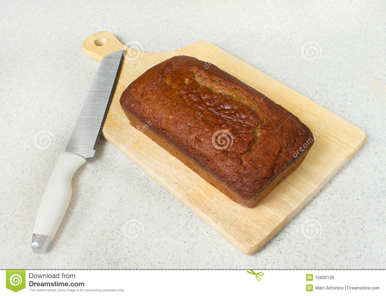 One Loaf Of Banana Bread On A Cutting Board With Knife On A Countertop
