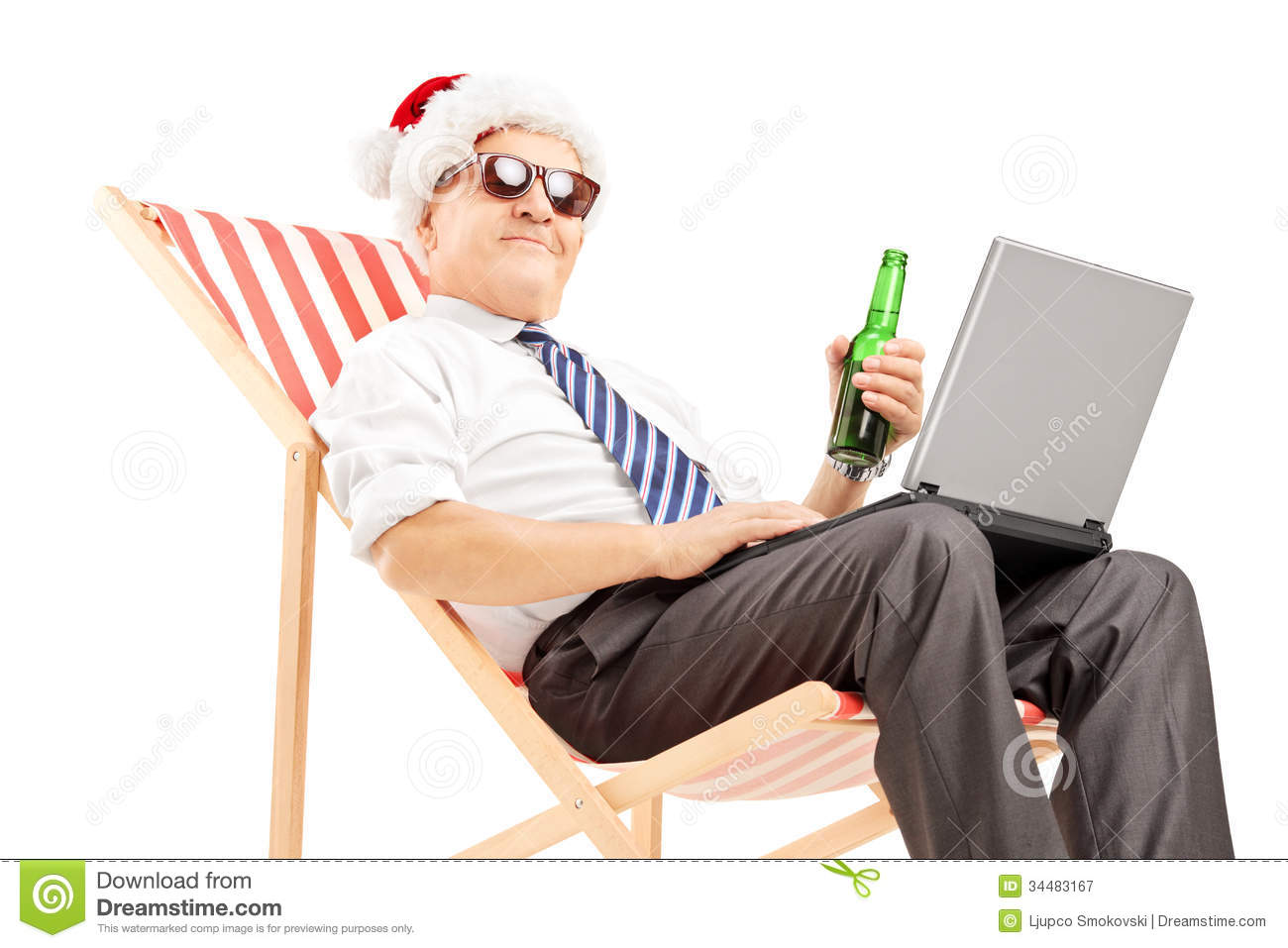 Mature Businessman With Santa Hat On A Beach Chair Drinking Beer