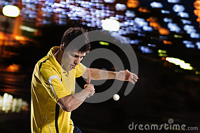 Young Sports Man Tennis Player In Play On Black Background With Night
