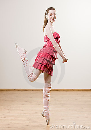 Ballerina In Frilly Dress And Leg Warmers Balancing On Toe In Dance