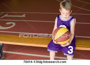 Sad Boy In Basketball Uniform Holding Ball While Sitting On Bench View