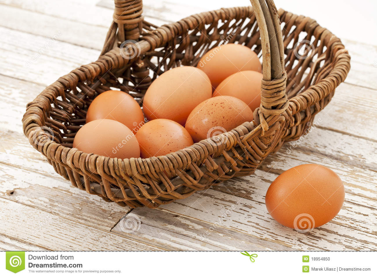 Basket Of Brown Chicken Eggs Against Grunge Wooden Table With White