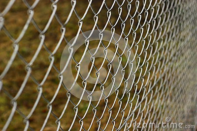 Silver Chain Link Fence Pattern With Grass On The Background