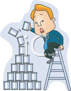 Grocery Clerk Teetering On A Ladder While Building A Pyramid Of