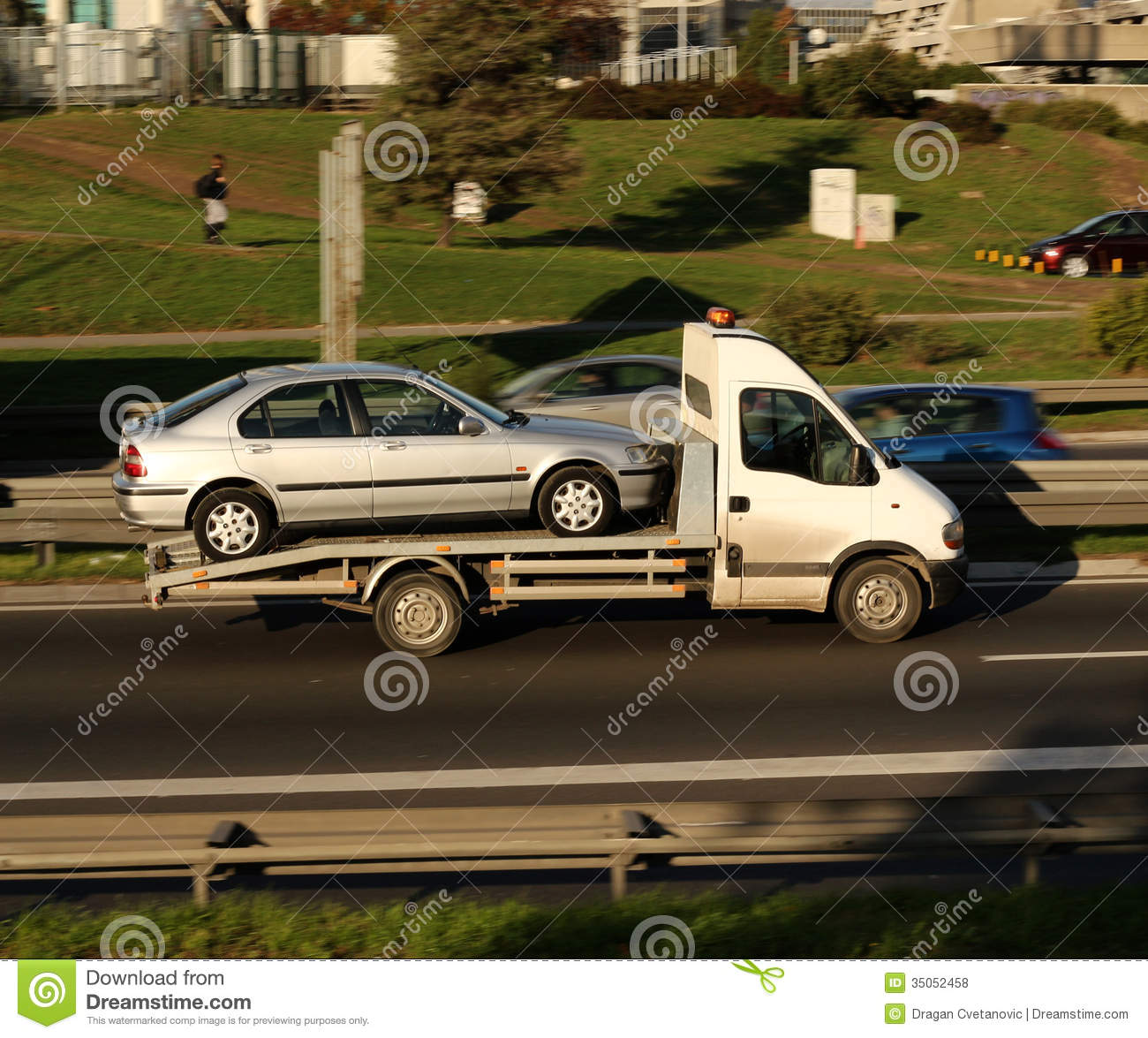 Silver Car Being Towed On A Towing Truck Speeding On A Highway