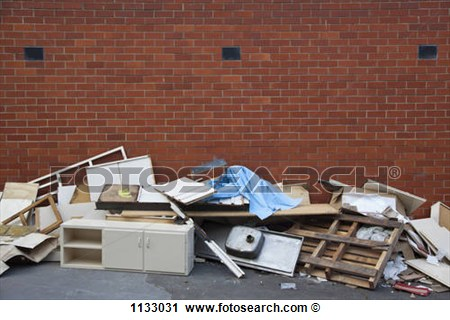 Broken Furniture And Scraps Of Garbage Piled Up Against A Brick Wall