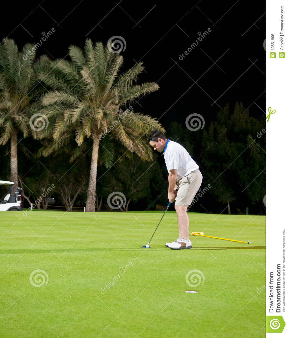 Male Golfer Prepares To Putt The Ball In The Hole During A Night Game