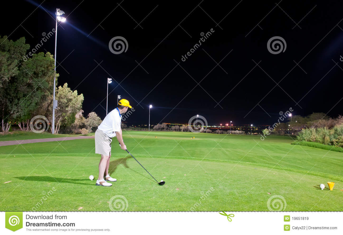 Male Golfer Tees Up On The Golf Course At Night