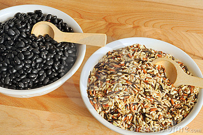 Bowls On A Cutting Board Containing Uncooked Wild Rice And Black Beans