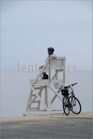 Picture Of Cyclist Resting In A Lifeguard Chair On A Deserted Beach