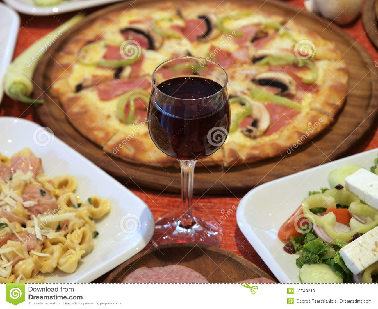Appetising Italian Feast Of Red Wine Pizza Pasta And Salad