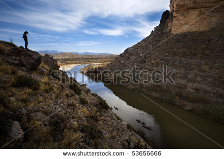 Cliffs Looking Over River At Canoes Down In The Water   Stock Photo