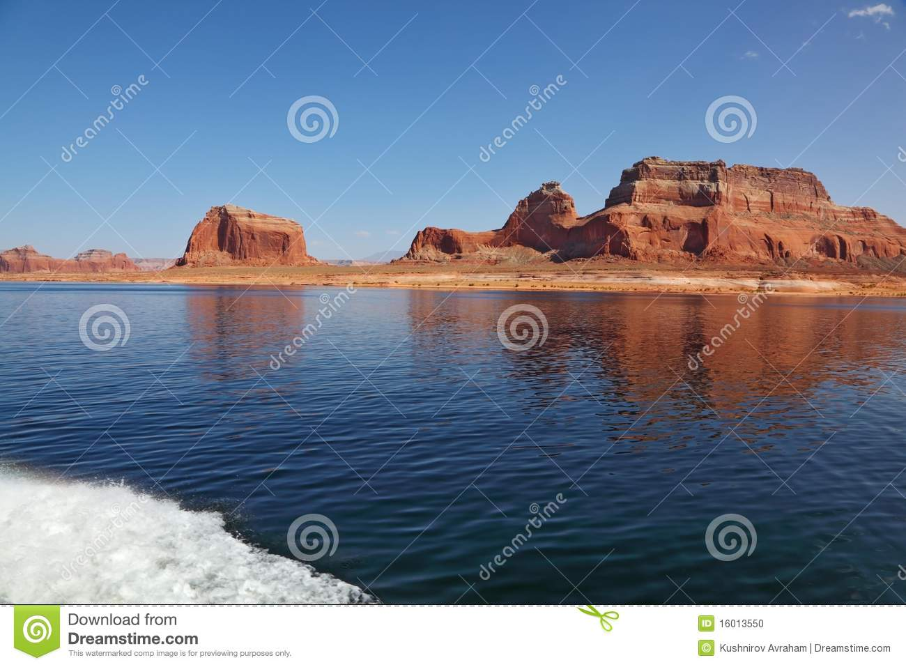 Picturesque Red Cliffs Reflected In The Smooth Water Of The Lake