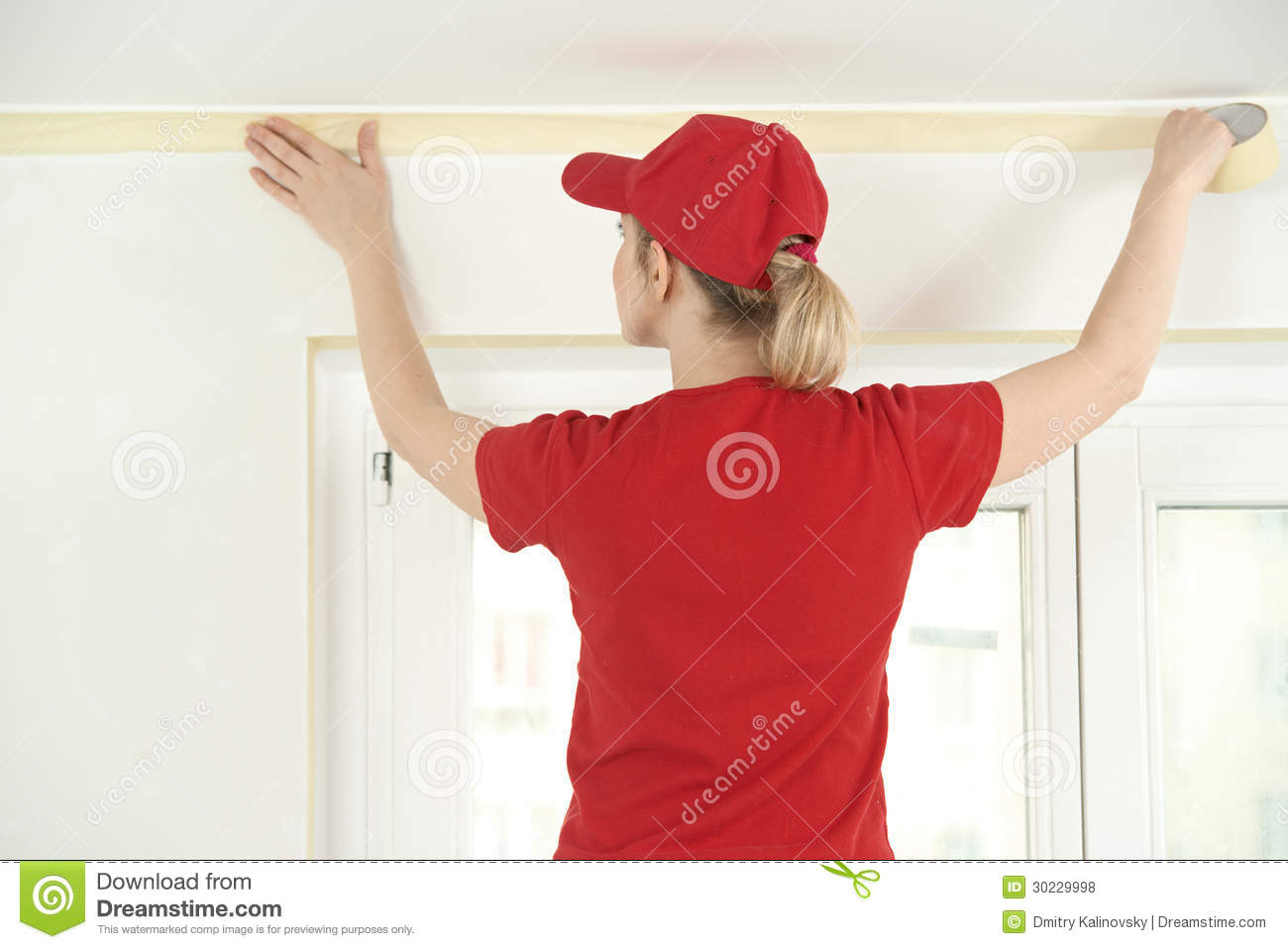 Woman Painter Worker Protecting Ceiling Moulding With Masking Tape
