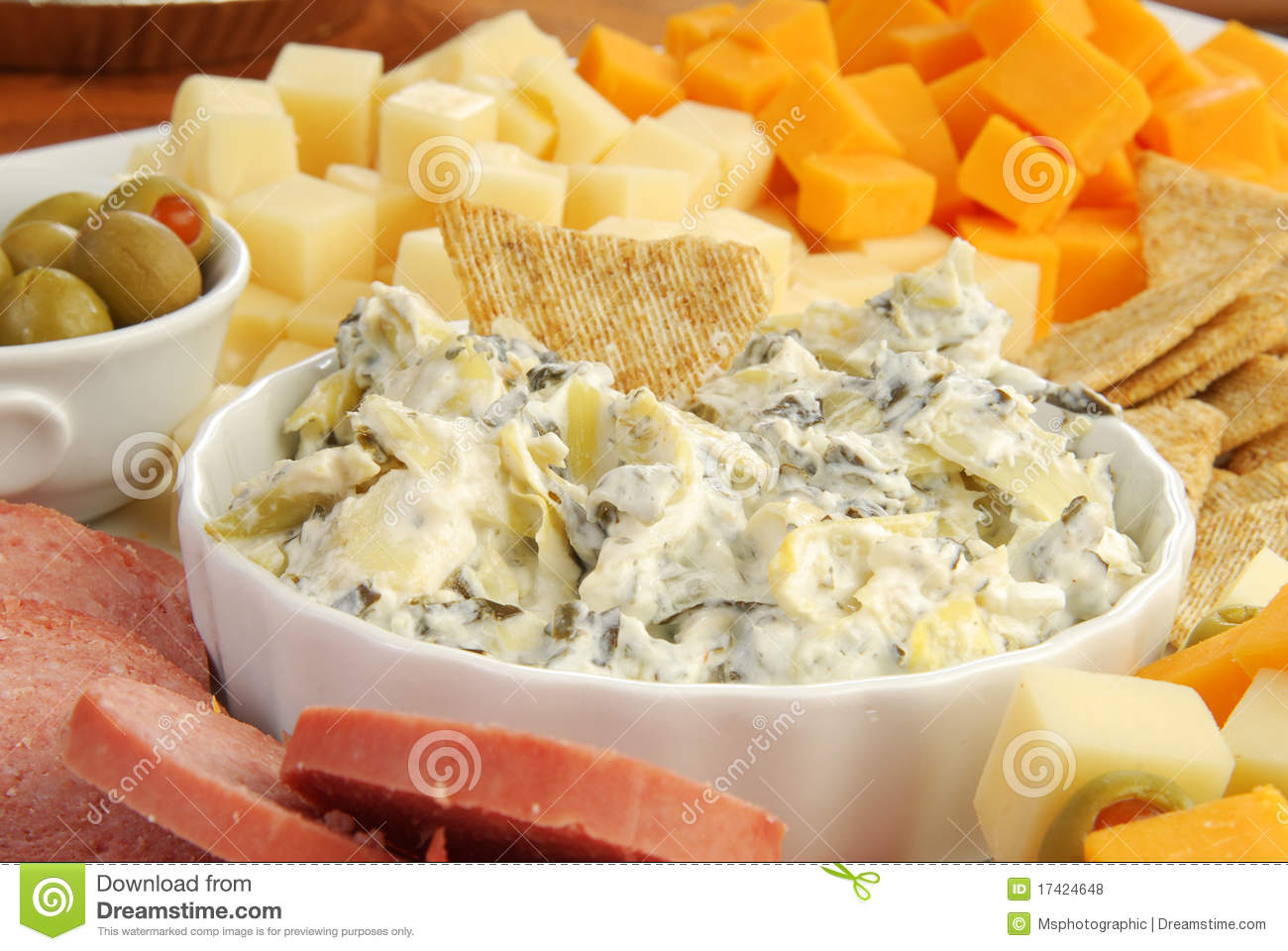 Of Spinach Artichoke Dip On A Plate With Crackers Meats And Cheeses