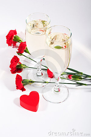 Two Glasses Of Champagne Carnations And Red Plastic Heart On White