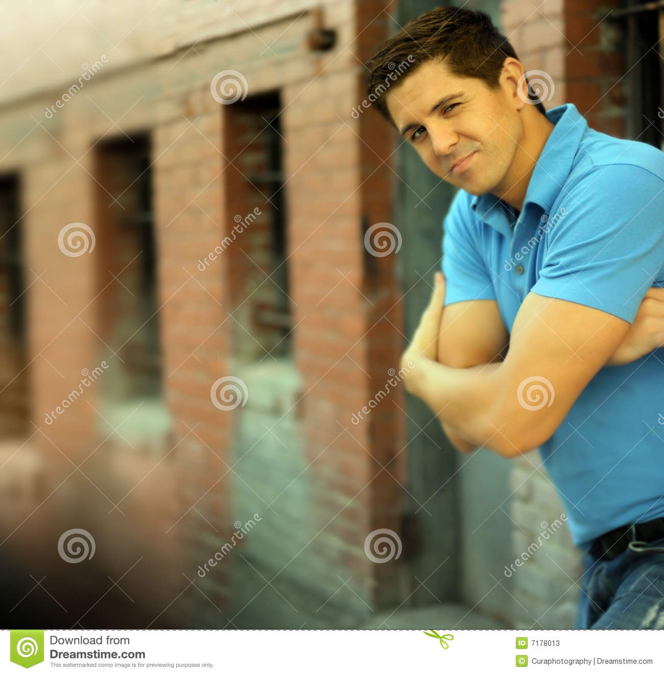 Of Young Good Looking Male Model With Folded Arms While Winking