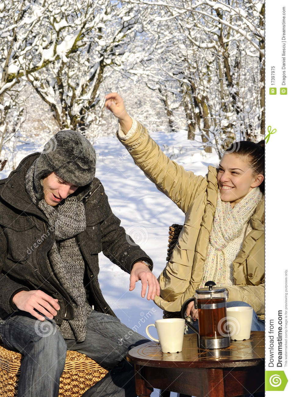 Young Man And Woman Celebrating Winter Season Cups With Tea On Table