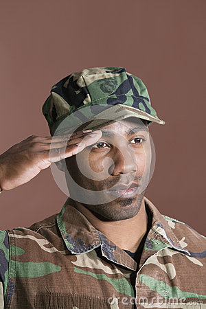 African American Us Marine Corps Soldier Saluting Over Gray Background